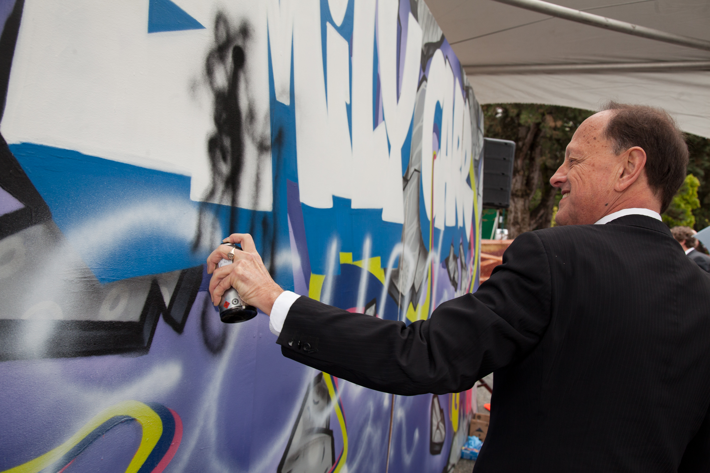Dr. Ron Burnett tags the graffiti wall at Emily Carr University's groundbreaking ceremony